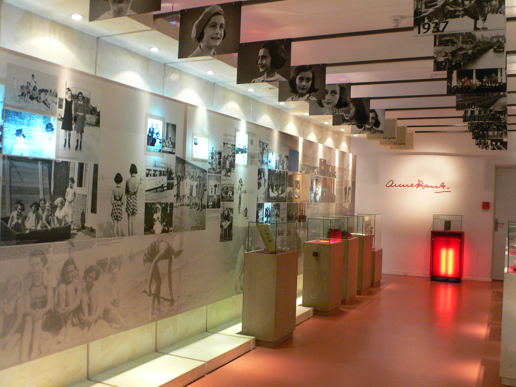 Inside Ann Frank Museum with photos of Ann in a white room