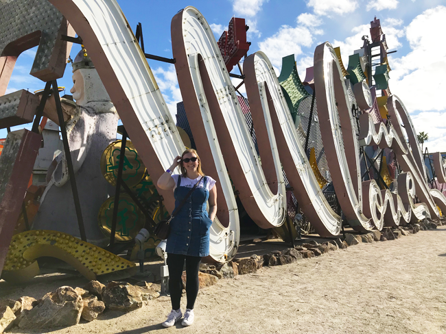 Mel in front of a neon sign at the neon sign museum, top things to do in downtown Las Vegas for non gamblers