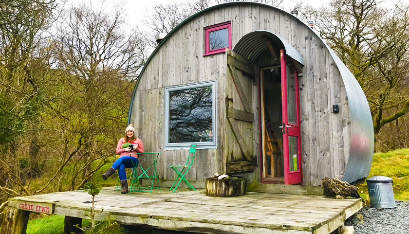 Mel sat in front of a small, off-grid cabin in the woods in Wales