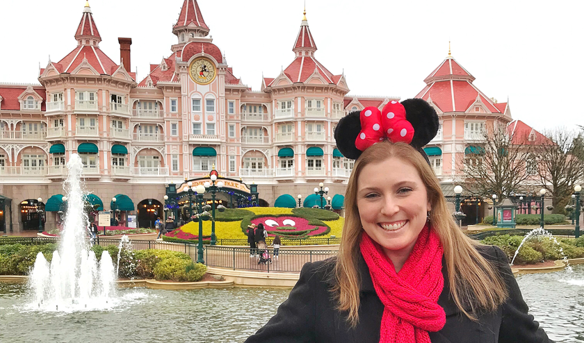 Mel in front of the entrance of Disneyland Paris with Minnie Mouse ears on