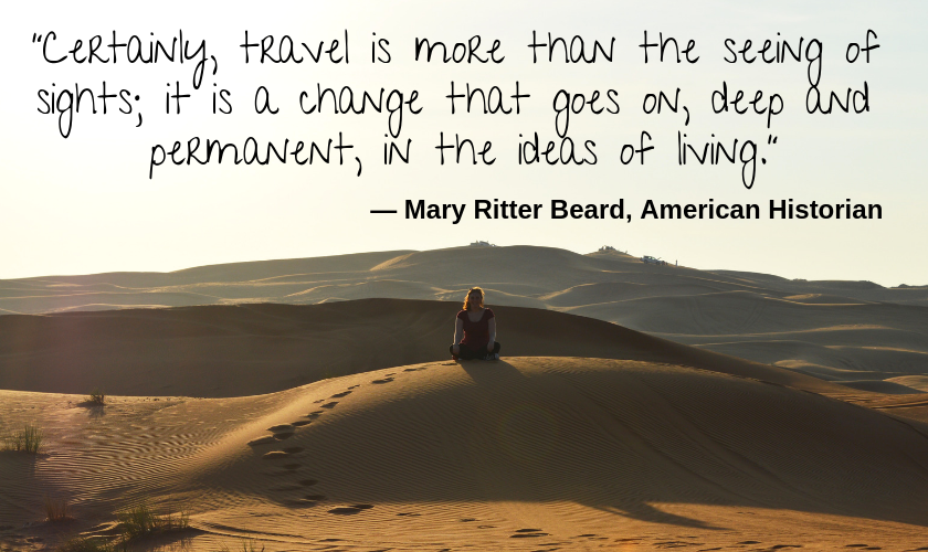 "Mel on top of a sand dune with her legs crossed in the Dubai desert with the quote ""Certainly, travel is more than the seeing of sights; it is a change that goes on, deep and permanent, in the ideas of living."" by Mary Ritter Beard, American Historian"