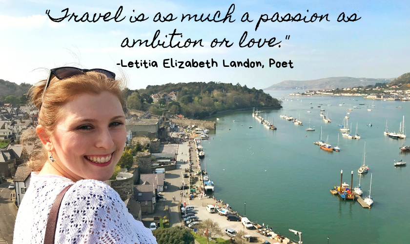 "Mel smiling in front of a harbour town in Wales on a sunny day with the quote ""Travel is as much a passion as ambition or love."" by Letitia Elizabeth Landon an English Poet and Novelist at the top of the image"