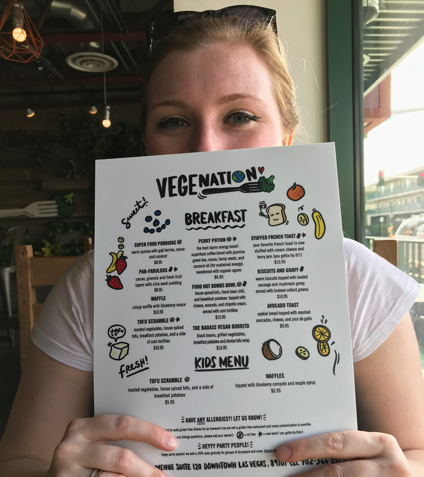 Mel holding up the Vegenation menu up to her nose, smiling at the food choices inside vegenation downtown Las Vegas