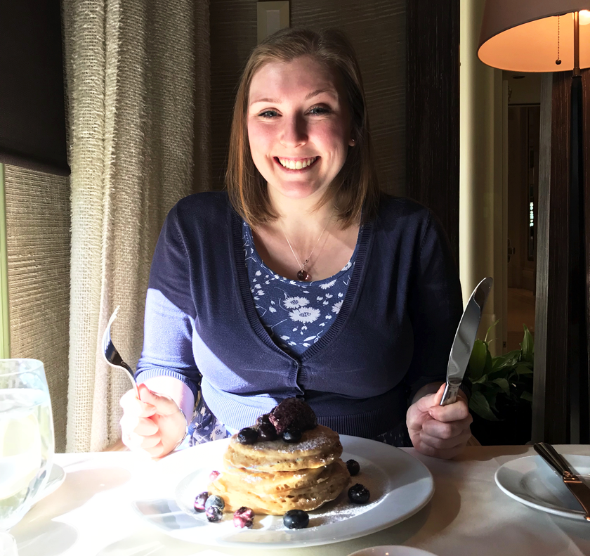 Mel wearing a blue dress and cardigan holding a knife and fork looking happy over blueberry pancakes at Tableau in the Wynn Hotel Las Vegas