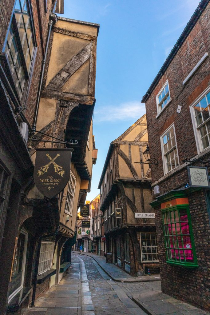 Medieval main street in York, UK with brown facades, windows and signs