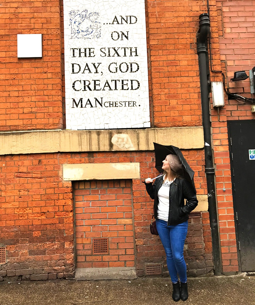 Mel from Footsteps on the Globe, in Manchester holding an umbrella under a sign that says: 'And on the sixth day God created Manchester', Why I took a year off blogging