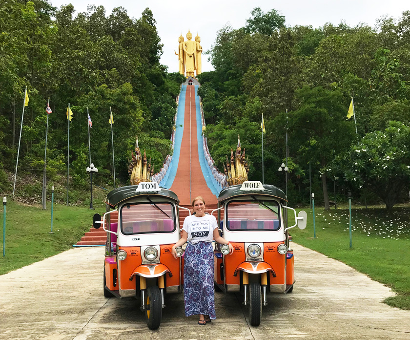 Mel from Footsteps on the Globe posing alongside two orange Tuk Tuk's in front on a long and high staircase leading to three gold buddha statues at the top of the hill in Chiang Mai in Thailand Breaking up, backpacking and beginning again