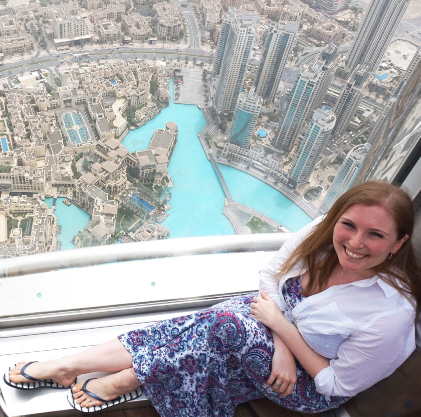 Mel from Footsteps on Globe on the 125th floor of the Burj Khalifa in Dubai laying down up against the deck floor window with the scenery below, Breaking up, backpacking and beginning again