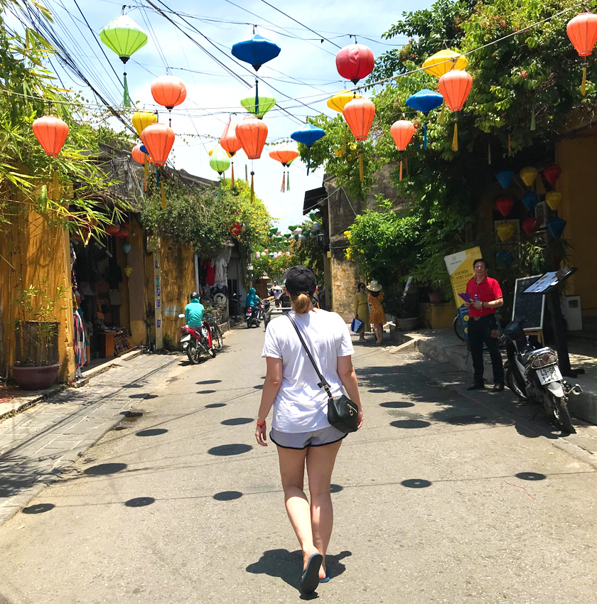 Mel from Footsteps on the Globe walking under colourful lanterns down a street in Hoi An in Vietnam