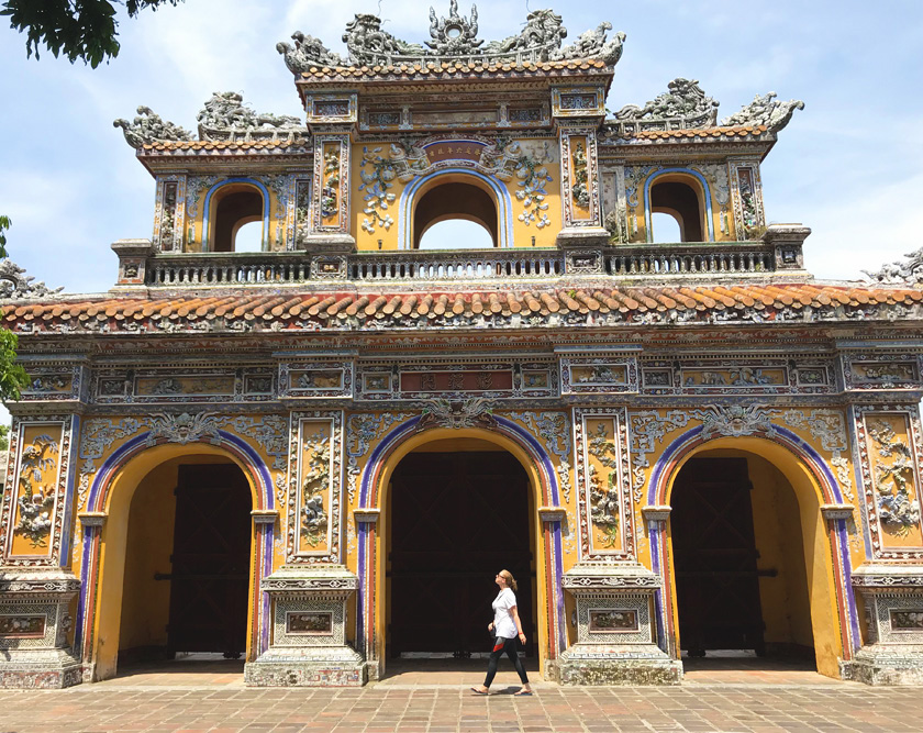Mel from Footsteps on the Globe walking in front of the Imperial Palace in Hue in Vietnam