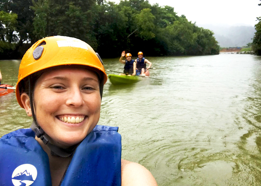 Mel from Footsteps on the Globe in a lifevest and yellow helmet taking a selfie whilst kayaking down the Nam Song River in Laos, Breaking up, backpacking and beginning again