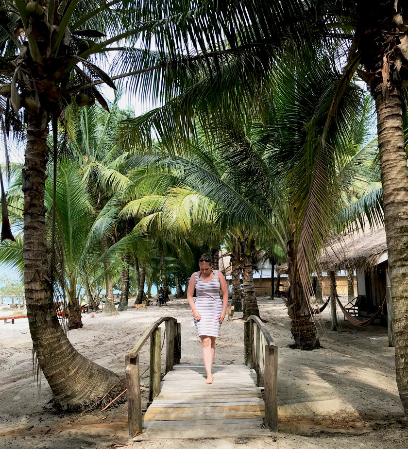 Mel from Footsteps on the Globe in a beige dress, bare foot and walking over a bridge with palm trees either side on a sandy beach on Koh Rong island in Cambodia, Breaking up, backpacking and beginning again
