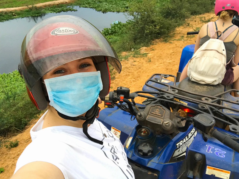 Mel from Footsteps on the Globe quad biking in Cambodia taking a selfie wearing a red helmet and face mask in Siem Reap in Cambodia, Breaking up, backpacking and beginning again