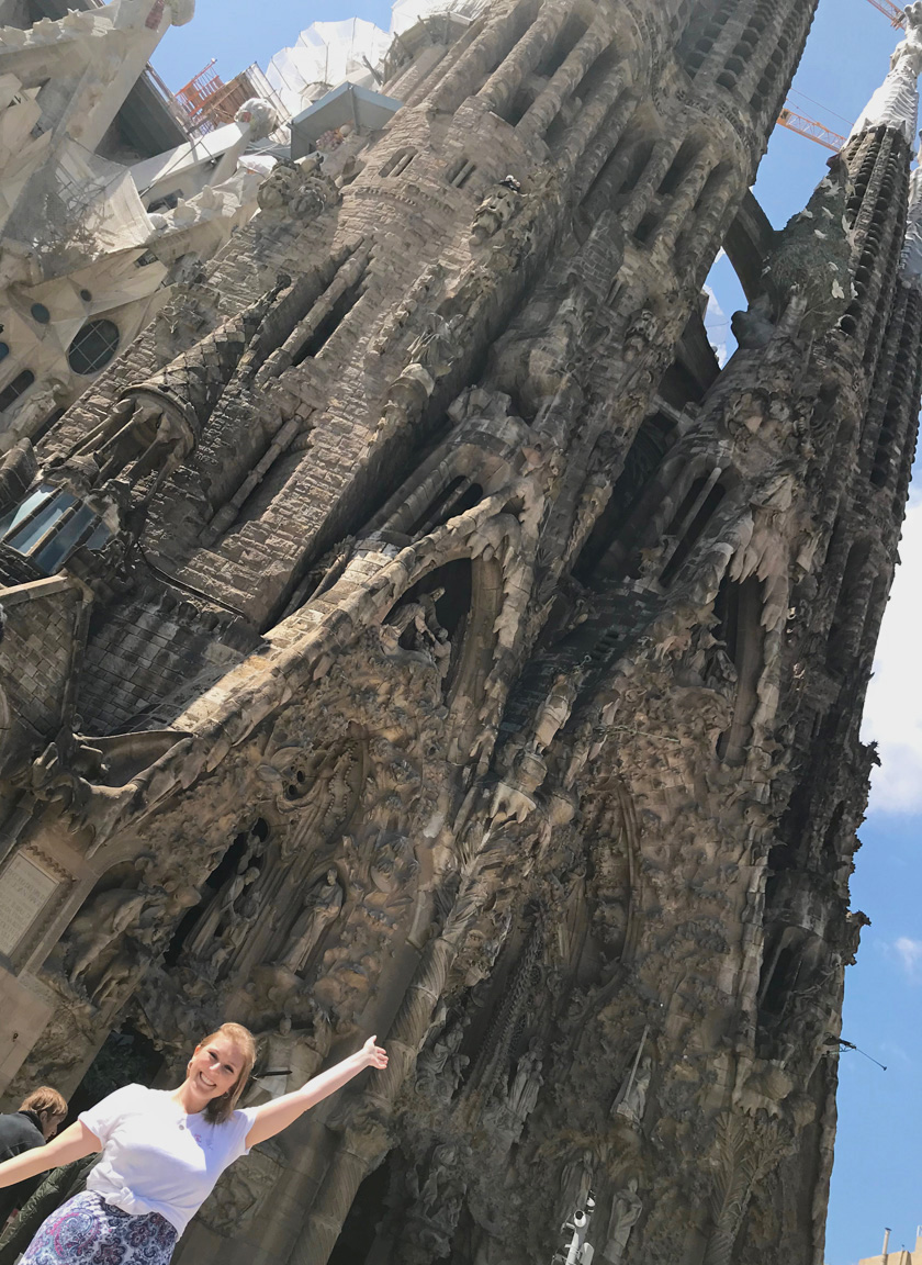 Mel from Footsteps on the Globe smiling and holding her arms up in front of the Sagrada Familia in Barcelona Spain with a sunny blue sky, Breaking up, backpacking and beginning again, Breaking up, backpacking and beginning again