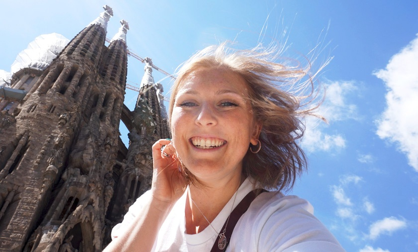 Mel from Footsteps on the Globe smiling in front of the Sagrada Familia in Barcelona Spain with a sunny blue sky, a year off blogging, Why I took a year off blogging: Breaking up, backpacking and beginning again
