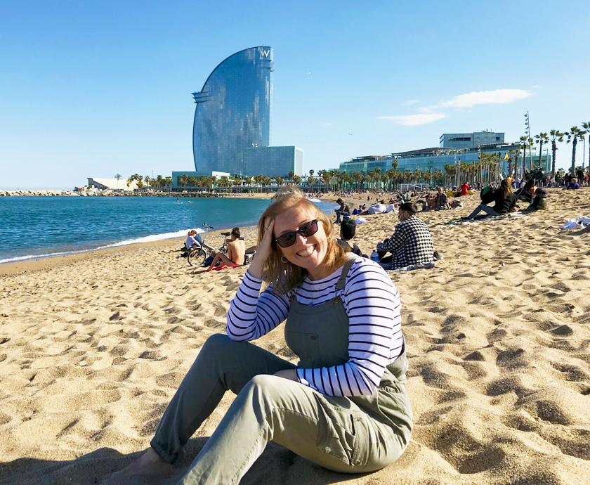 Mel from Footsteps on the Globe sat on Barcelonetta Beach in Barcelona Spain in front of the W Hotel in green dungarees and sunglasses, Breaking up, backpacking and beginning again
