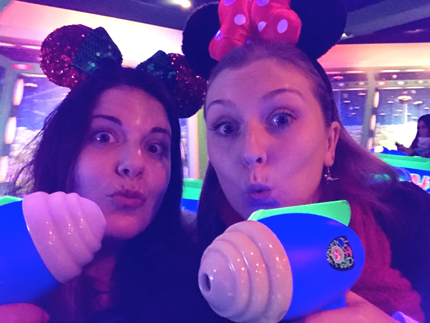 Mel from Footsteps on the Globe and her friend Tami holding up Buzz Light Year guns on the Buzz Lightyear ride at Disneyland Paris, Reasons to go to Disneyland Paris