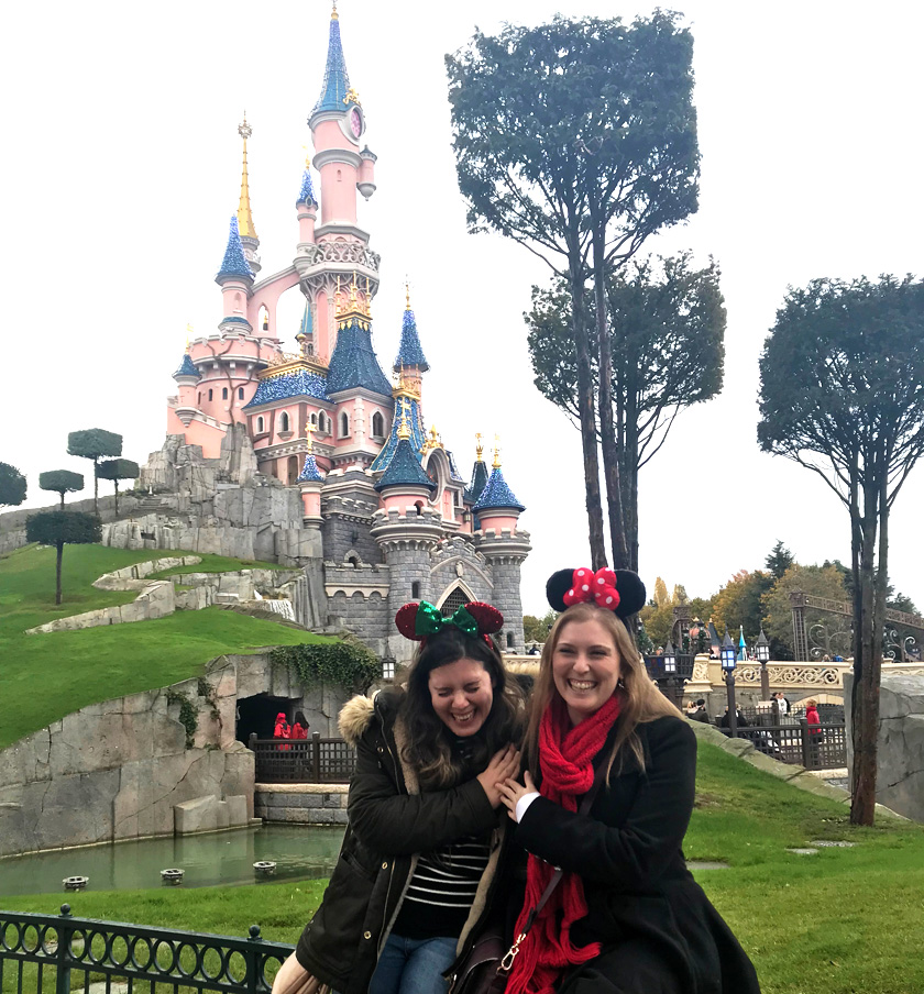 Mel from Footsteps on the Globe smiling in front of sleeping beauty's castle at Disneyland Paris with her friend Tami, Reasons to go to Disneyland Paris