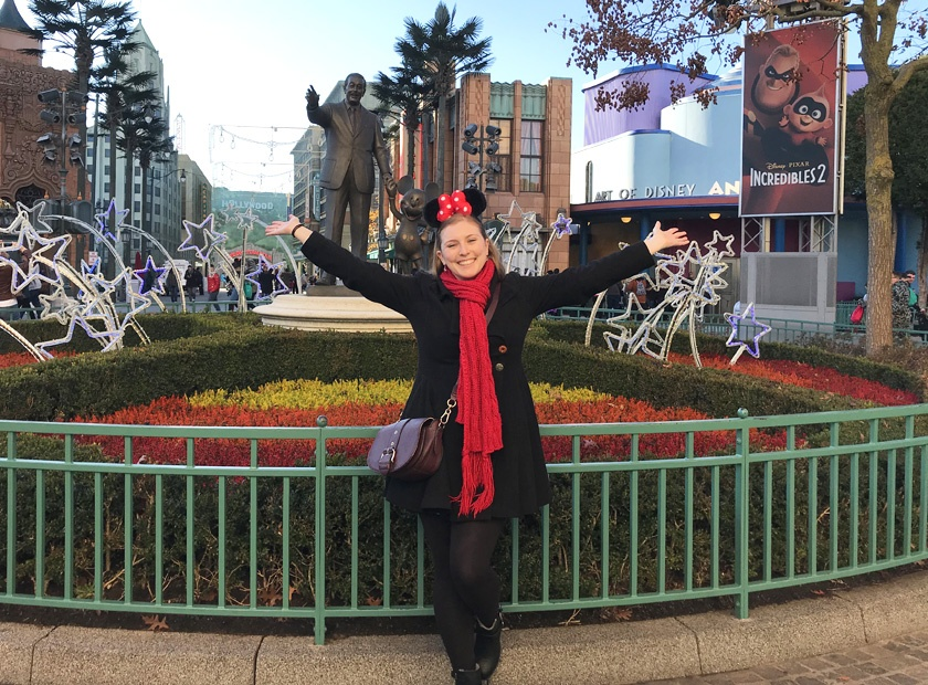 Mel from Footsteps on the Globe smiling in front of a Walt Disney and Mickey Mouse statue at Disneyland Paris, Reasons to go to Disneyland Paris