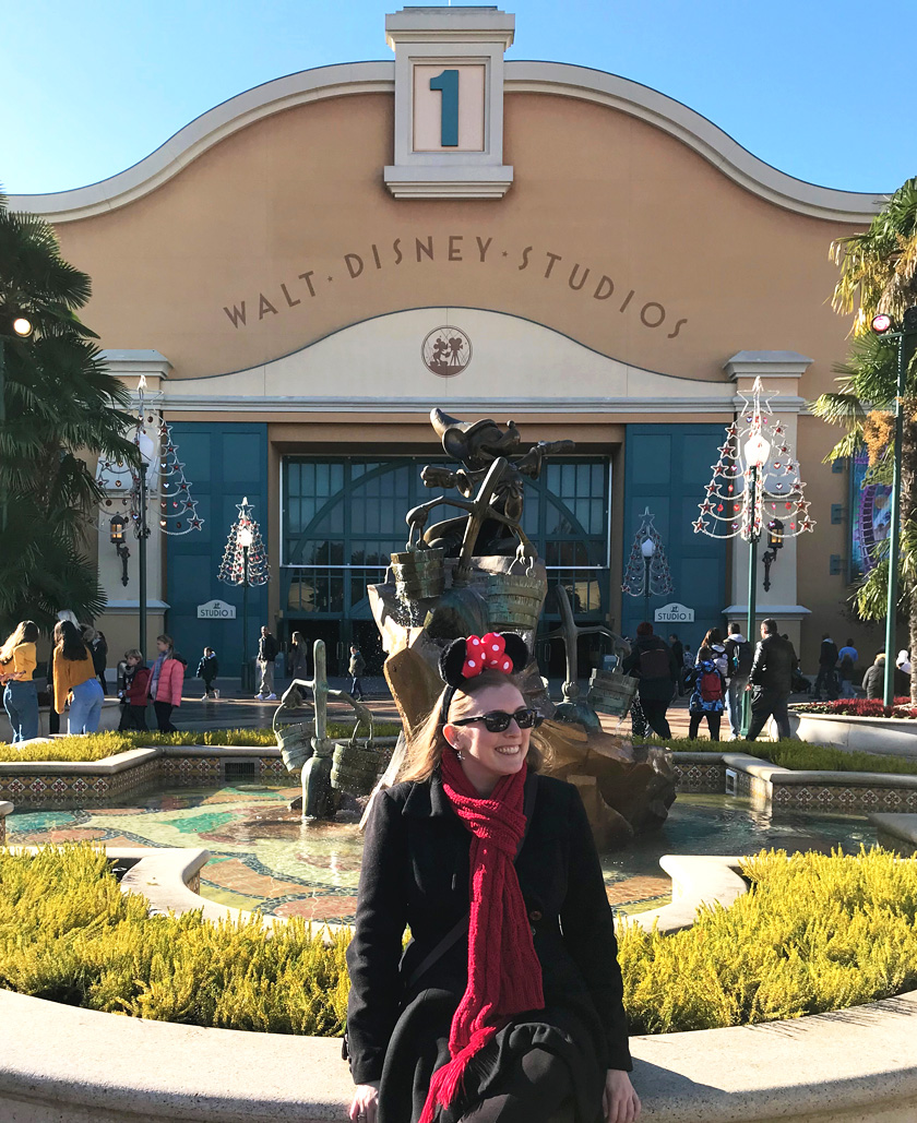 Mel from Footsteps on the Globe smiling in front of a Mickey Mouse statue at Disneyland Paris Studios, Reasons to go to Disneyland Paris