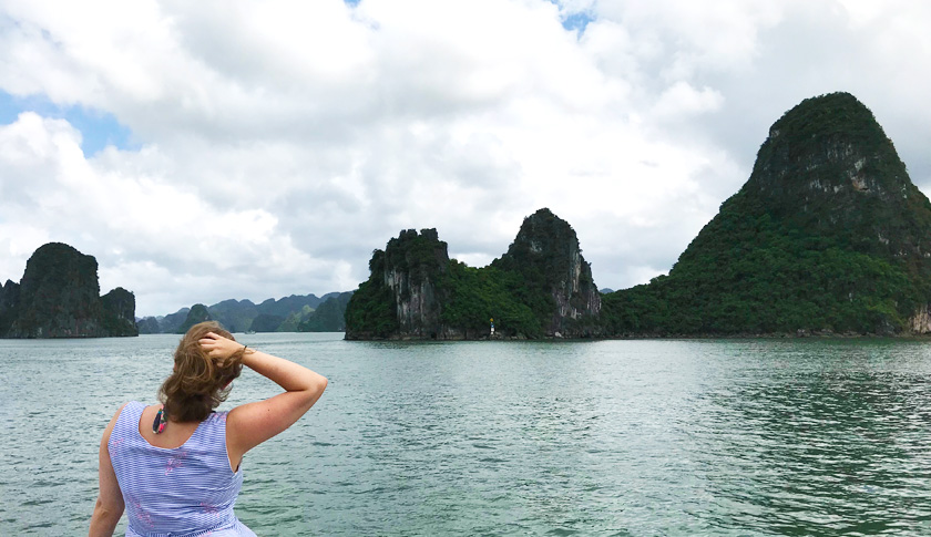 Mel from Footsteps on the Globe in Halong Bay in Ha Long City in Vietnam with a sunny blue sky and mountains