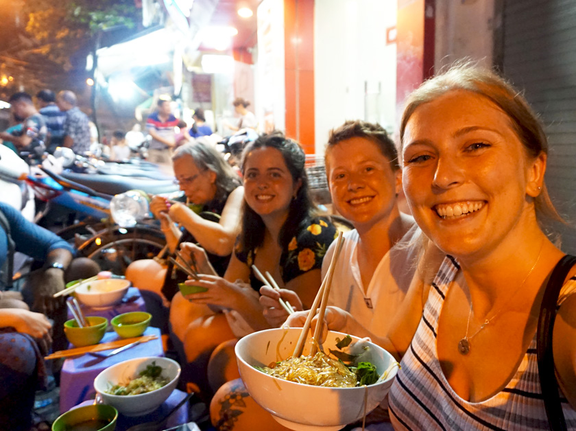 Mel from Footsteps on the Globe eating noodles on the streets of Hanoi in Vietnam