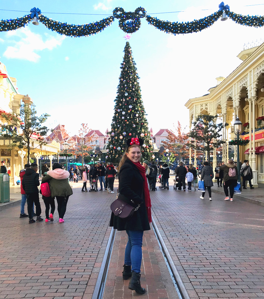 Mel from Footsteps on the Globe smiling in front of a Christmas tree down Main Street USA at Disneyland Paris, Reasons to go to Disneyland Paris