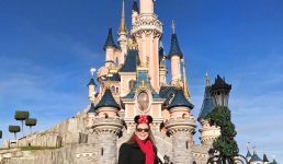 Mel from Footsteps on the Globe smiling in front of the princess castle in Disneyland Paris with a sunny blue sky, reasons to go to Disneyland Paris