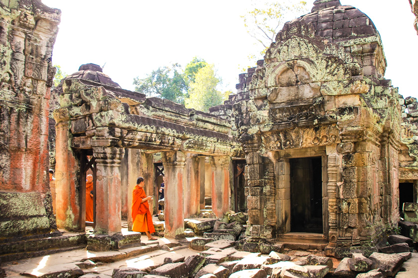 Buddhist monks dressed in orange robes walking between temples.