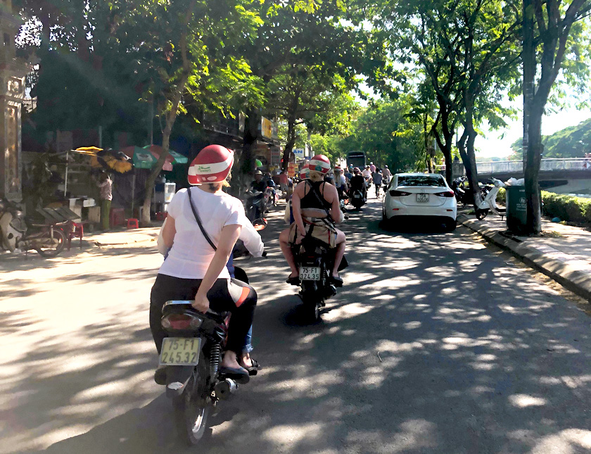 Mel from Footsteps on the Globe on the back of a motorbike driving down a busy street in Hue in Vietnam