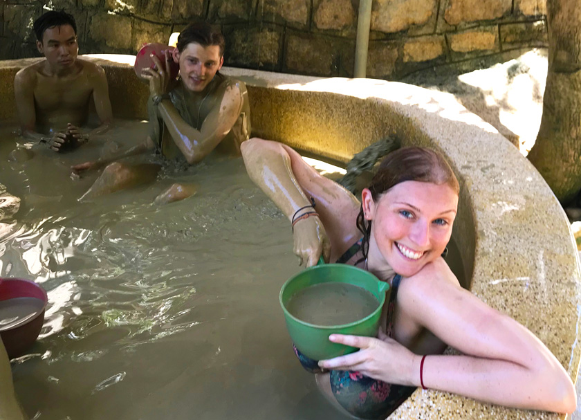 Mel from Footsteps on the Globe holding a bucket of mud in a mud bath at a Mud Spa in Nha Trang in Vietnam