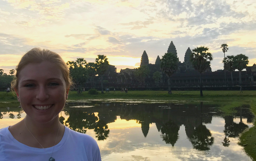 Mel from Footsteps on the Globe smiling in front of the temple and the lake at sunrise.