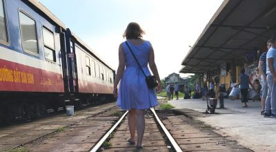 Mel from Footsteps on the Globe walking away down the train tracks next to a train in Vietnam at sunset
