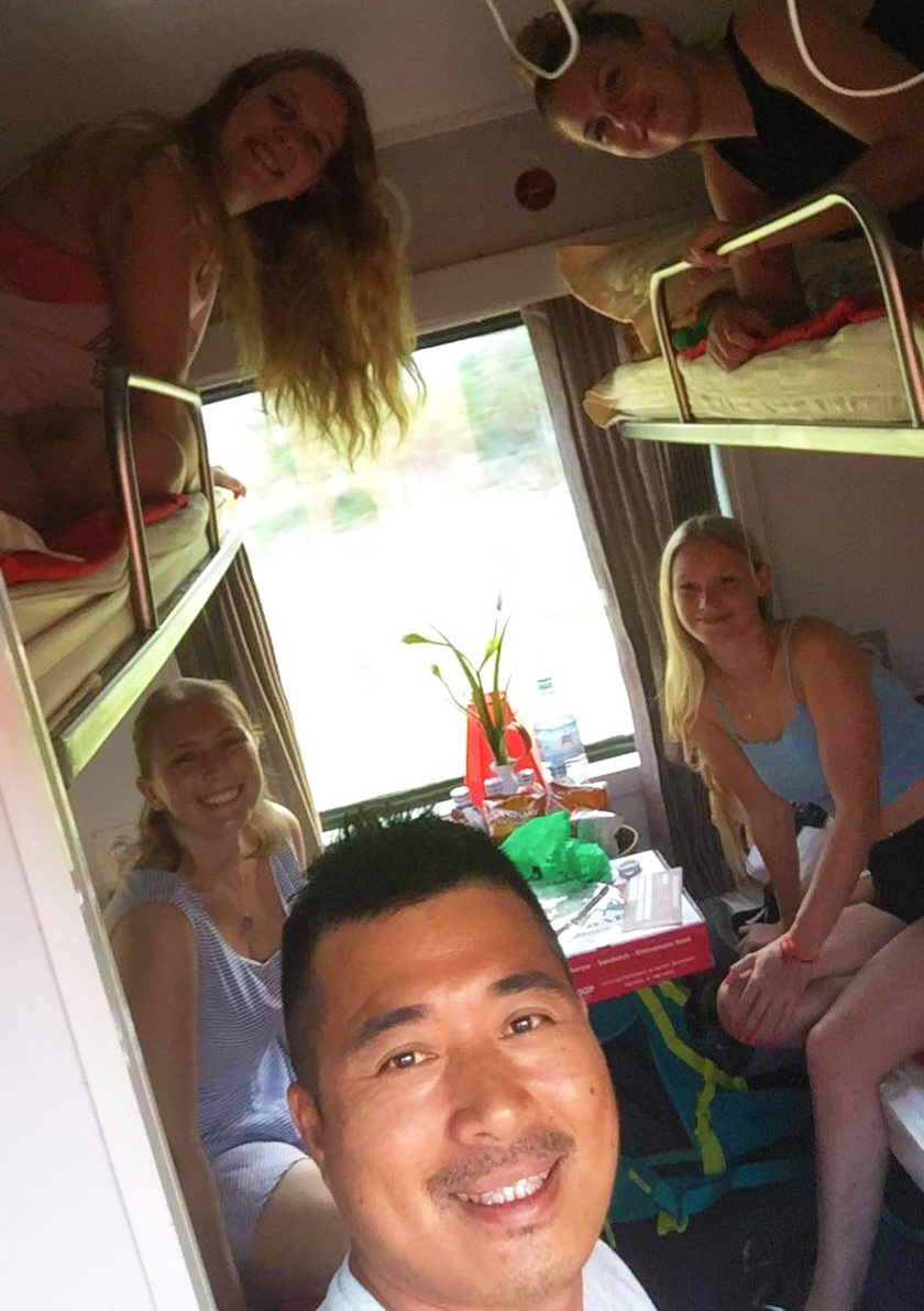 Mel from Footsteps on the Globe with friends each sat on a bunk on an overnight train in Vietnam taken selfie style from the door to the room