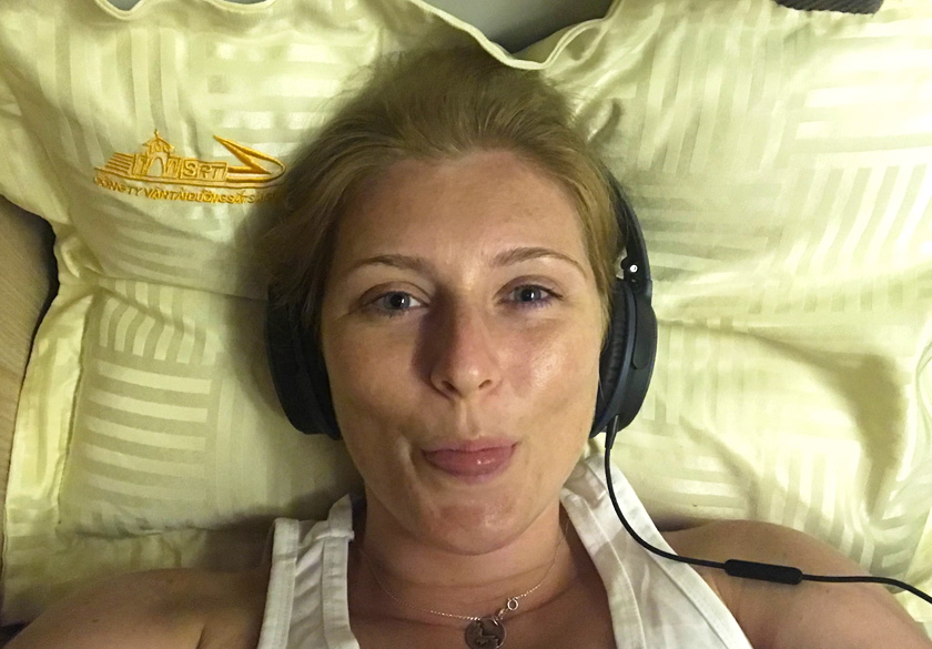Mel from Footsteps on the Globe lying on the bottom bunk on the overnight train in Vietnam with headphones on resting on a yellow pillow and sticking her tongue out taking a selfie