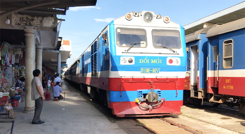 Blue, white and red train coming into the station in Vietnam with people waiting on the platform to board