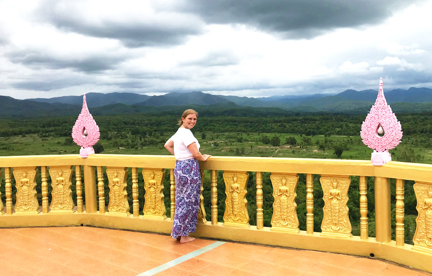 Mel from Footsteps on the Globe on a golden balcony at a temple in Mae Wang with mountains and greenery in the background