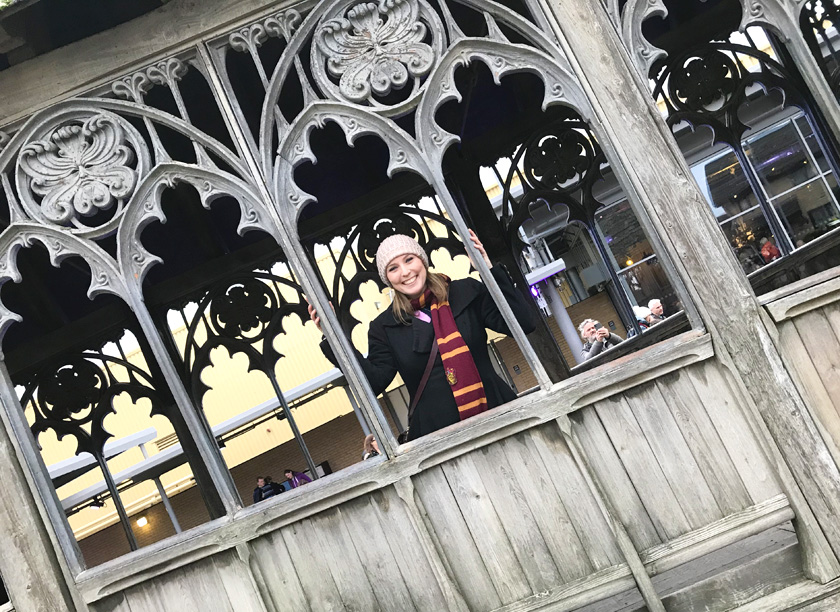 Mel from Footsteps on the Globe on smiling from the window of the Hogwarts Bridge