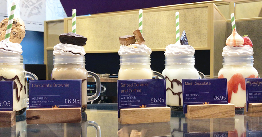 Row of five different non-vegan milkshakes on the counter at The Chocolate Frog Cafe