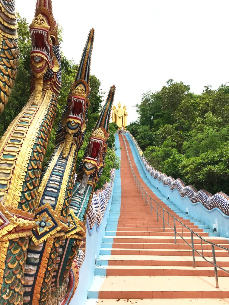 Golden dragons next to a red and blue staircase leading to three golden buddha statues at the top of a hill