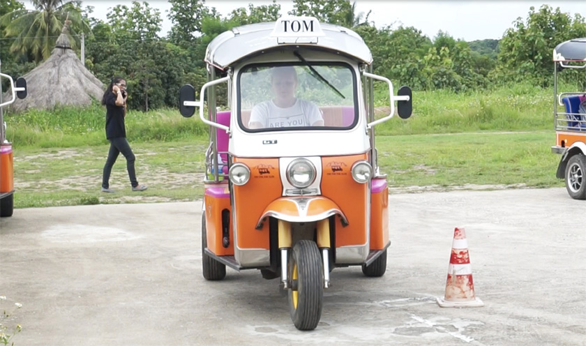 Mel from Footsteps on the Globe at the test centre driving an orange Tuk Tuk towards the camera with a cone on the right side of the Tuk Tuk