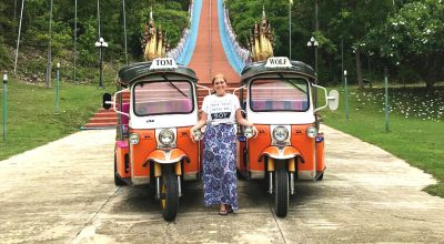 Mel from Footsteps on the Globe standing betweentwo orange and white tuk tuks in front of a temple's red and blue stairs in Chiang Mai Thailand