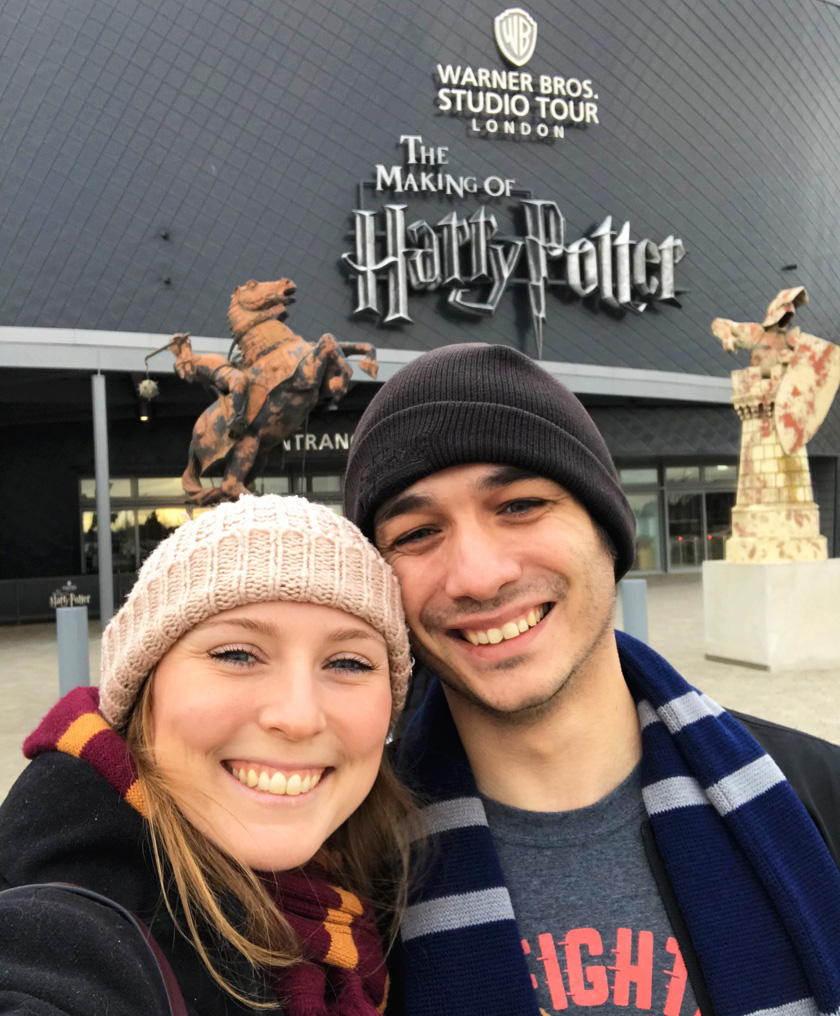 Mel from Footsteps on the Globe and her boyfriend smiling outside the front of the Harry Potter Studios London