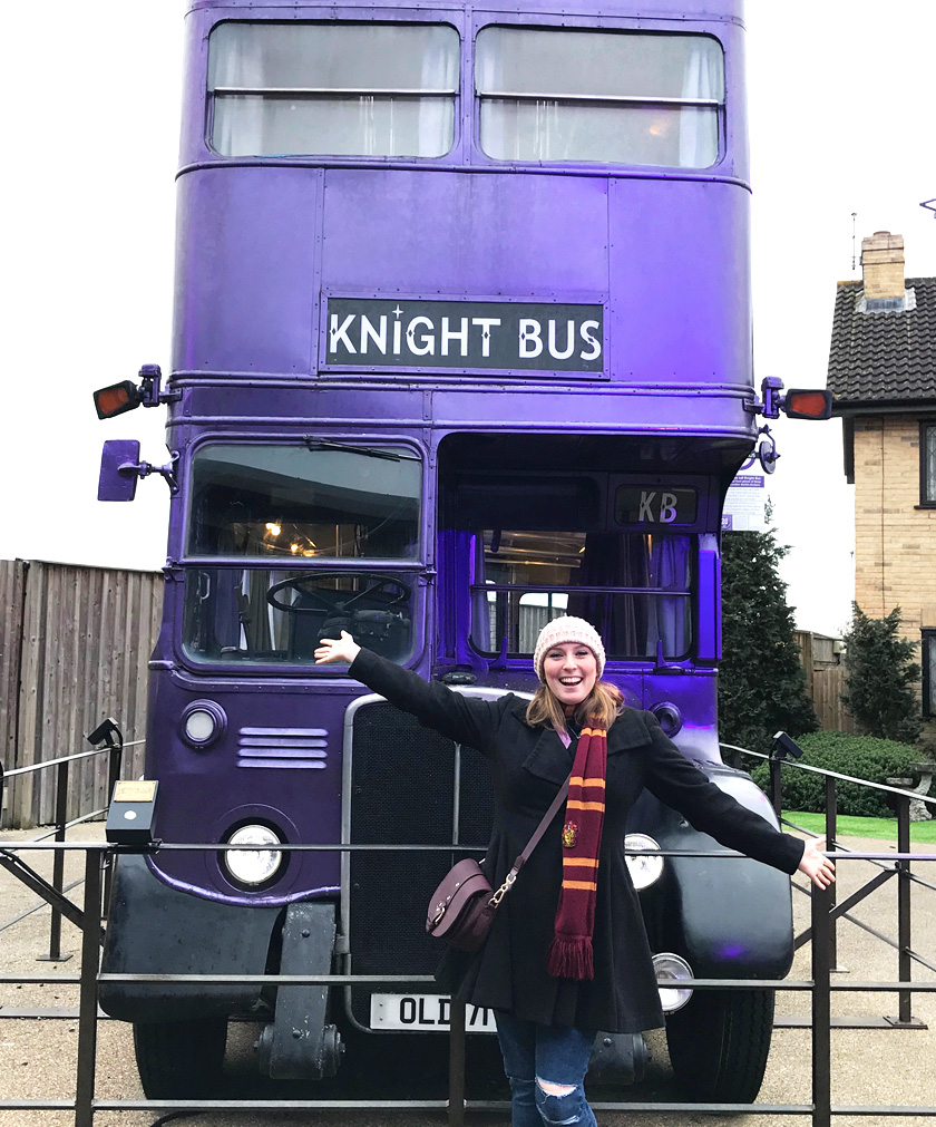Mel from Footsteps on the Globe with her arms outstretched in front of the purple Knight Bus on the backlot of The Harry Potter Studios London