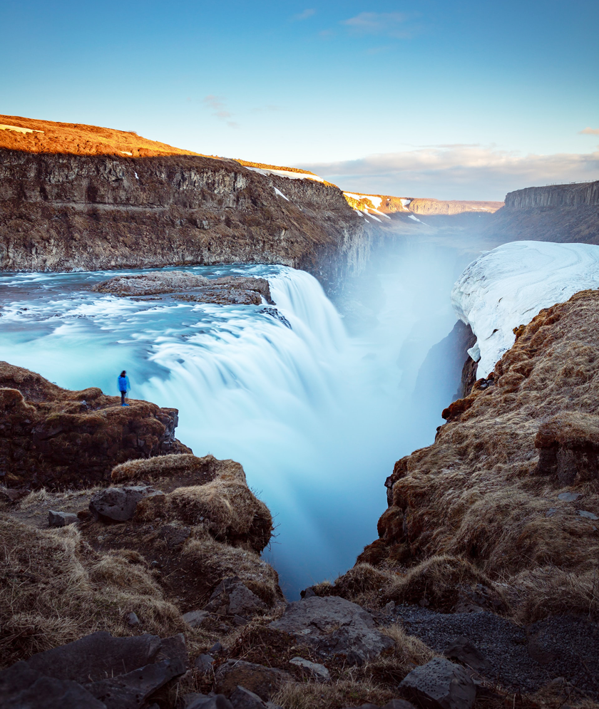 Woman standing on the edge of a huge waterfall in Iceland with mountains and blue skies behind her