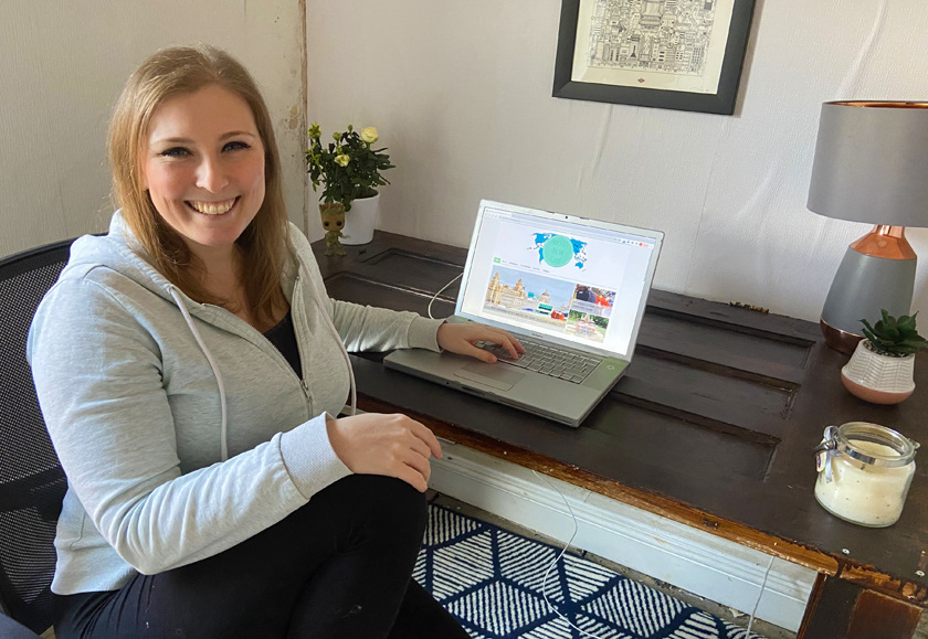 Mel sat at her laptop with Footsteps on the Globe website up