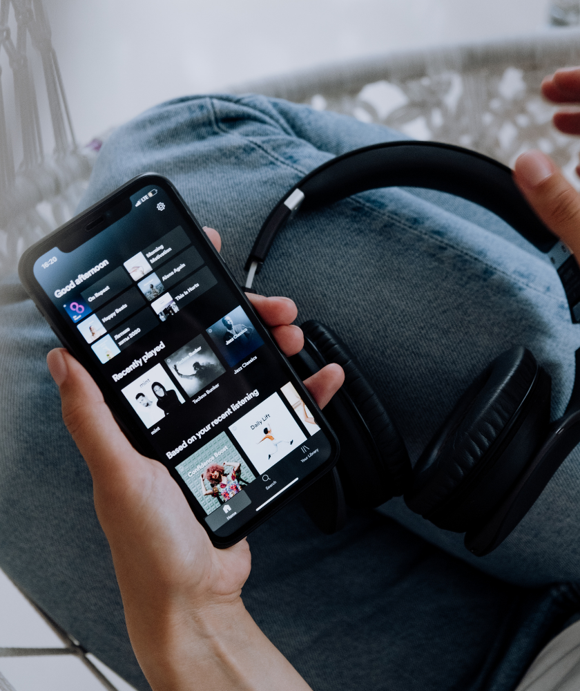 Woman holding headphones and her phone with Spotify on the screen