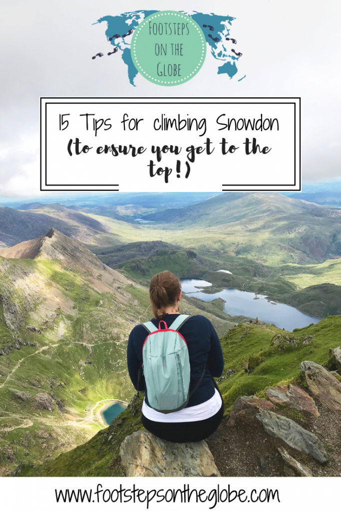 Mel sat on a rock with her back to the camera with her backpack on at the top of Snowdon looking out onto the horizon with green hills and blue lakes in the background - Pinterest image.