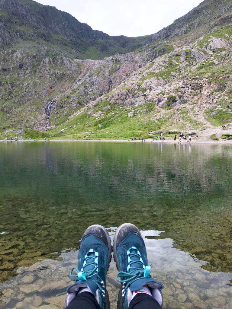 Mel sitting beside the Lake at the bottom of Snowdon snowing off her scuffed green hiking boots after descending to the bottom of Snowdon.