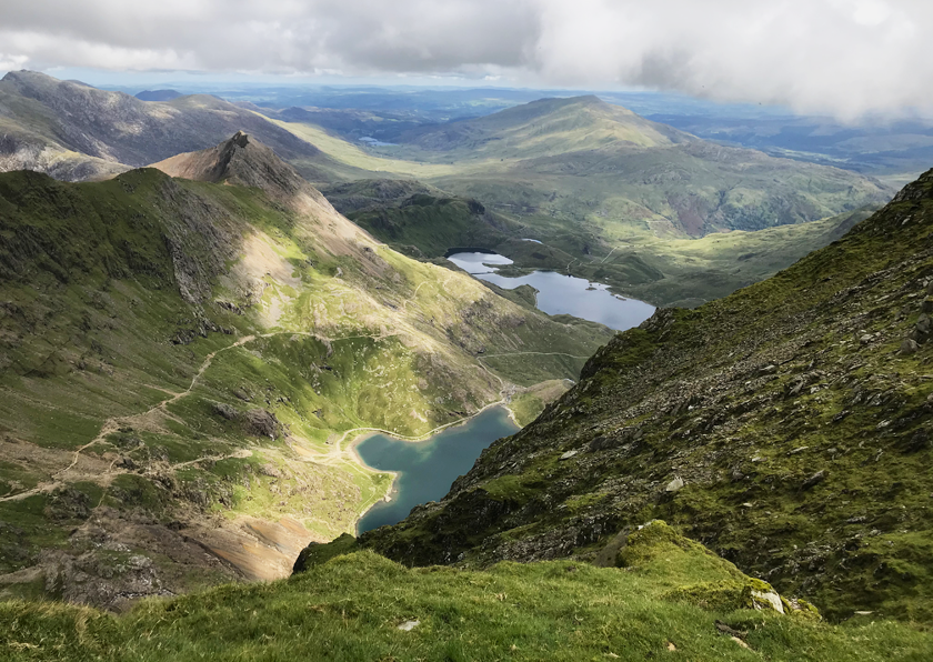 Landscape view from the top of Snowdon with green hills, lakes and clouds.